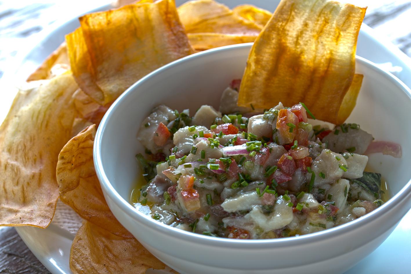 Ceviche de peixe branco com cebola roxa, todas as ervas do mundo e chips de batata doce